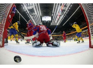 Russia's Andrei Vasilevski #30 looks as Sweden players celebrate after taking a 1-0 lead in preliminary round action at the 2014 IIHF World Junior Championship. (Photo by Andre Ringuette/HHOF-IIHF Images)